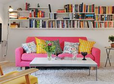 Bright couch, colorful textiles, simple walls and table, great book storage