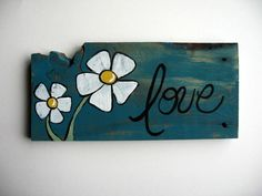 """This piece of barn wood is reclaimed from an Iowa farm. It is painted in teal with daisies and the word, """"Love.""""    This barnwood measures approx. 12 inches long and 5.5 inches wide."""