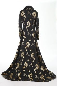 An Alexander McQueen trained evening coat, 'Angels & Demons' collection, Autumn-Winter, 2010-11. with metal dogtag label, and size 46, of steel grey figured silk in 18th century style, brocaded in gold and burgundy blooms, the curved lapels with self-pleat