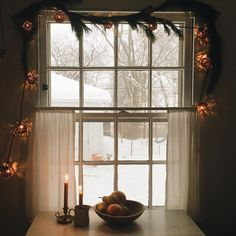 Winter wonderland inspiration. Kitchen window strung with lights, sow outside, and candles lit on table in country house via Amelia Markgraf. #cozyChristmas #scandinavianchristmas