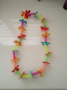 Hawaiian lei playgroup craft. String, jumbo straws cut into pieces and flowers punched out if paper