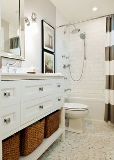 Gorgeous bathroom with white vanity, seagrass basktes, frameless mirror, marble floors, white subway tile and striped shower curtain!