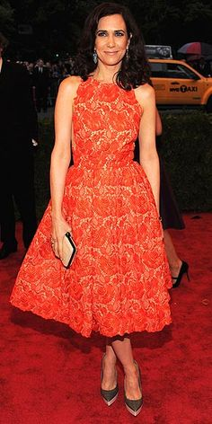 KRISTEN WIIG in a full-skirt orange Stella McCartney lace number with two-tone platform pumps, also by the designer, and a putty-colored clutch at the 2012 Met Gala