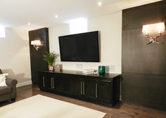 Refined by Design - Interior Design Toronto   - Custom wood wall panels and ebony stained AV unit with wall mounted TV and recessed speakers & circa lighting sconces
