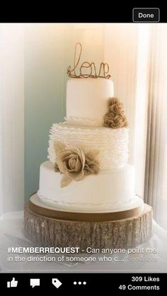 White cake with wooden board and hessian flowers