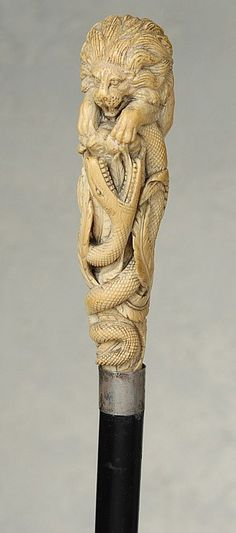 """A marvelous ivory cane of a lion and snake. It depicts in marvelous detail, a male lion sitting atop a foliage-laden tree stump confronting a vicious, open-mouthed snake. There is a smooth cartouche where a name or initials could have been inscribed, as well as a 7/8"""" smooth silver collar. It is perhaps English, ca 1865, and it may be allegorical with the lion representing the British Empire and the snake representing her foes."""