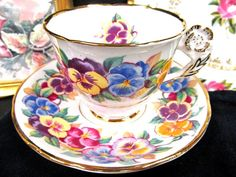 OFFERING THIS PRETTY JUST FANTASTIC TEA CUP AND SAUCER THIS WAS MADE IN ENGLAND BY ROYAL STAFFORD SUPER PANSY FLOWERS AND A NICE FLOWER HANDLE AS WELL MADE OF A FINE BONE CHINA WITH NO WEAR AND MADE AROUND THE 1930S TALL AND FLARED AND FOOTED BASE AMAZING PIECE CALLED VIOLA PLEASE