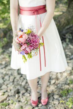 noni noni Brautkleider 2013   knielanges hochzeitskleid mit schwingendem rock und rosa- rotem gürtel mit schleife und bändern zum binden, v- ausschnitt mit breiten trägern, fascinator, runde brautschuhe emma in rosa gefärbt (Foto: Hanna Witte)