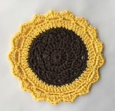 I have crocheted this little sunflower mandala style table mat coaster using a cotton yarn. The centre is dark brown and the outer rounds are a golden sunshine yellow. The finished mat measures approx. The yarn is machine washable in . Sunflower Mandala, Crochet Sunflower, Crochet Mandala, Yellow Sunflower, Crochet Gifts, Crochet Hooks, Crochet Table Mat, Small Mats, Dorset Buttons