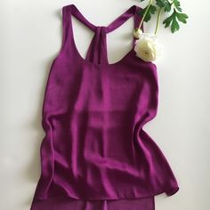 BCBGMAXAZRIA Edita Tank Gorgeous amethyst, silky tank in a loose flowing fit. Slim cut out at the back and a modern high-low hem (which can easily tuck into skirts as the fabric is thin). Scoopneck, racerback.  Poly. **One very small spot on lower front. Barely noticeable (photo) otherwise excellent condition. BCBGMaxAzria Tops Tank Tops