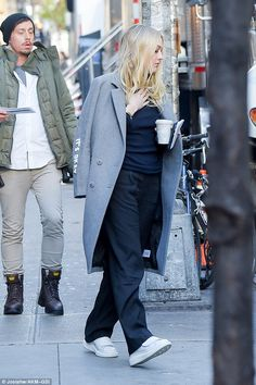 Wrapped up: The 22-year-old cut a low-key figure as she sauntered clutching a hot beverage with a grey trench coat draped over her shoulders