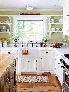 Cottage Color Scheme:Taking cues from Bungalow style, this kitchen features simple Shaker-style cabinetry and open shelving. In keeping with this genre's dark palette including red, olive, and stained wood, this kitchen exhibits a fresh take on the deeper colors replacing darker green with light celery on the walls. Wood is painted white. In keeping with tradition, olive shows up on the kitchen island and bronze hardware is indicative of the 1920s style.