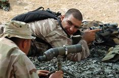A training sniper confers with his spotter.