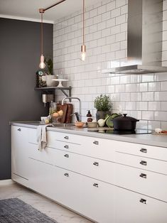 A pretty timeless white and grey kitchen - unfussy cupboards, subway tile kitchen wall, dark grey paint and stunning yet simple hanging copper lights.