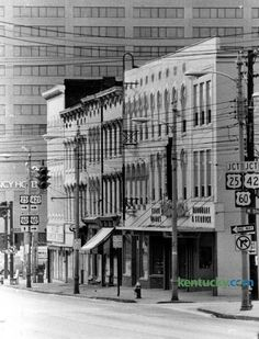 These buildings facing North Broadway between Main Street and Short Street, seen in January 1978, would become part of the block that made up Victorian Square, a commercial district that is on the National Register of Historic Places. Tenants on this bloc in 1978 included PinkstonÕs Hardware and Service, at right. Next was PinsktonÕs Turf & Leather Goods and then, CoxÕs Hotel. The building on the corner of West Main was part of H.H. Leet Furniture Company. It became the home of DeSha's…
