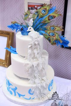 blue and white wedding cake with peacocks