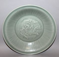 CHINESE LONGQUAN-STYLE CELADON PORCELAIN DRAGON DISH, moulded to its centre beneath the glaze with a sinuous dragon amidst cloud scrolls, the base partially unglazed, 11.75in d.