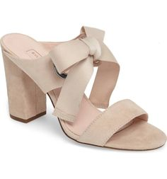 A lush bow loops through exaggerated eyelets atop a double-strapped suede sandal, perched on a lofty, wrapped block heel.