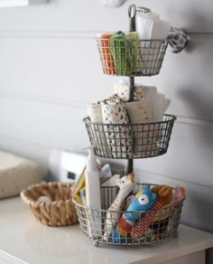 Use a tiered kitchen basket in the nursery as the perfect spot to stash washcloths, burp cloths and lotions. Clever! - projectnursery.com