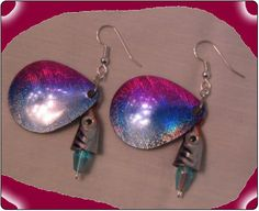 http://diginanchors.com/EarringsAlure_BlueMarlin - Costume jewelry made from fishing lures of brilliant colors to create a unique but beautiful pair of earrings. Painted blue, purple, and silver the blade has a flashy finish with a crystal bead supporting the matching fish head on a silver wire. Has surgical stainless steel earwires coated with gold or silver plating. It is 2 and 1/4 inches long and 1 inch wide.