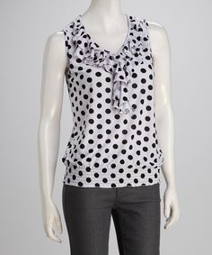 Nothing jazzes up an ensemble or a mood faster than a spunky polka dot print. Banded along the bottom and boasting rows of feminine ruffles framing the neckline, this sleeveless top satisfies any need for sweet fashions with a vintage-inspired twist.Measurements (size S): 25'' long from high point of shoulder to hem92% polyester / 8% spandex
