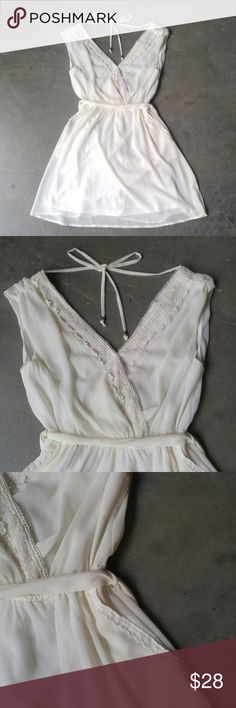"A'GACI White V-Neck V-Back Dress A'GACI dress, size medium, in excellent condition! Features crochet detail on neckline and pockets. Fully lined. Waist tie belt, elastic waist. Tie at back of neck/shoulder. V-neck and v-back. Ivory white color is more white than ivory. 18"" pit to pit, 12"" elastic unstretched waist, 33"" length. 100% polyester. No trades. No modeling. Make a reasonable offer. Thanks! a'gaci Dresses Mini"