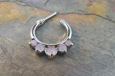16 gauge pink opalite crystal septum ring clicker nose piercing. This is made of 316L surgical steel with prong set faceted centered CZ gems, a
