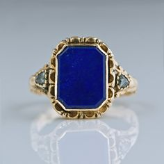 This Georgian era ring features a tabular rectangular lapis lazuli flanked by pear-shaped, rose-cut diamonds. Its back contains an unusual locket, surrounded by hand engraving. Hand wrought details embellish the mounting throughout. Stamps indicate Continental origin