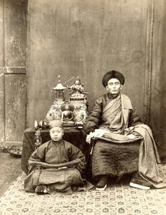 "An image of a ""lama,"" or Tibetan Buddhist monk, and his pupil. Both subjects hold prayer beads and bundles of ""sutras,"" or scripture, in their laps. On the table behind them are bronze sculptures and sacred Tibetan ritual objects, including a skull cup with a bronze Buddha and a statue of Kali, the goddess of Time, Power, and Destruction. This is one of the earliest photographic portraits of a religious figure in Peking."