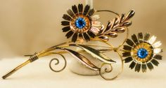 Vintage flower brooch with blue stones - metal is pink gold color combined with yellow gold color. The brooch is about 4.5 inches high and