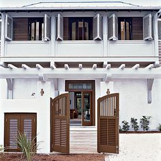 Entryway Gates: Brown shutter-style front gates mimic this home's sliding plantation shutters and continue the neutral color scheme.