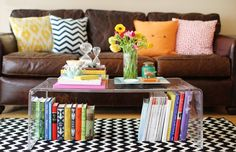 lucite coffee table + colorful books displayed underneath