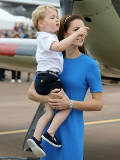 July 8, 2016: The tattoo is the world's largest military air show, held at the Royal Air Force (RAF) base at Fairford, southwest England. It was a blustery and busy day for the Royal Cambridge family. This image shows Prince George being held by his mummy Catherine, Duchess of Cambridge. ~ Photo by Getty Images.
