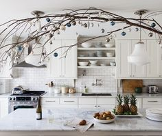 Designer Ingrid Oomen adds warmth to her white bistro-style kitchen during the winter months by hanging natural branches from the ceiling. Photo by Donna Griffith. From houseandhome.com.