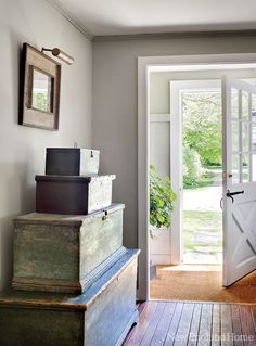 primitive painted trunks in shades of faded blues and greens decorate a farmhouse entry hall  .......GLITTERFARM