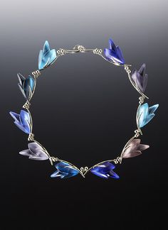stunning!!  Linda MacNeil, Floral Series 2005: Bouquet Edition, Acid polished blue and purple transparent glass laminated to mirrored glass. Polished 18k white gold.