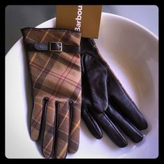 """✨NWT✨ Barbour Leather Gloves NWT Barbour women's brown leather gloves with one of their signature tartan/plaid patterns on the outer side. Beautiful and soft dark brown leather on the inner side. Small white thread is visible on the left glove index finger, but not noticeable unless you know where to look for it (see picture). The ruler is difficult to see, but the glove measures approx 8.5"""" at the longest point x 3.5"""" wide at the bottom with a 4.5"""" long thumb. Never worn. Make an offer…"""