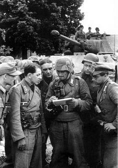 https://flic.kr/p/fiYjUK | Panzerkampfwagen V Panther Ausf. A (Sd.Kfz. 171) | Des éléments de la Panzer-Lehr près de Tilly-sur-Seulles (à l'ouest de Caen) le 9 juin 1944. On appréciera notamment les différentes tenues qui sont portées par ces hommes de la 130. Panzer-Division. Courtesy pics5.imagezone.org/key/%20Panzer%20Lehr%20Uniforms