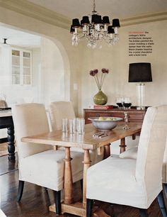 Slip covered parsons chairs, darker table.  Lower the lighting (the scale is too small for this room).