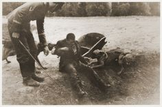 A German sets his two dogs upon a Jewish forced laborer, who is sitting on the side of a trench.