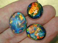 Three black opals showing two tones of body color. The Australian valuing system recognizes nine degrees of body tone. The gems at right would be graded the oval to the left Photo: Cody Opal Rare Gemstones, Minerals And Gemstones, Rocks And Minerals, Natural Gemstones, Australian Black Opal, Rocks And Gems, Stones And Crystals, Gem Stones, Gemstone Jewelry