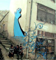 """アフガニスタンの街中の壁にスプレーを吹きかける女性グラフィックアーティストShamsia Hassani.彼女はアフガニスタンの街中の壁に鮮やかな色のスプレーでブルカを被った女性を描きます。アフガニスタンを""""戦争""""ではなく""""アート""""の国として知ってもらいたいと語る彼女は長引く戦争で疲れきったアフガニスタンの人々の心を色鮮やかのグラフィックアートで癒し、芸術は戦争に勝ことを証明してくれるでしょう。"""