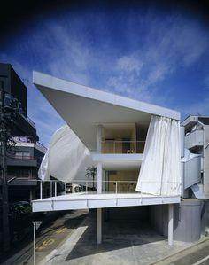 Curtain Wall House - Tokyo 1995. La démarche de Shigeru Ban détonne dans le paysage architectural mondial. Il a d'abord signé une profusion de riches demeures privées au Japon entre les années 1980 et 1990, où des structures de béton géométriques et épurées s'ouvrent sur l'espace environnant – l'une d'elle est seulement fermée par un immense rideau en toile qui faseille au vent. Avant de se tourner vers des projets beaucoup moins lucratifs.