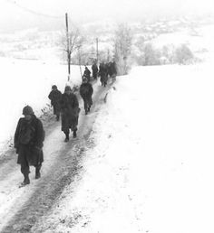 Men of the 83d Infantry Division, U.S. Army, hike through snow to join an armored force in an attack on the Nazis near Malempré.
