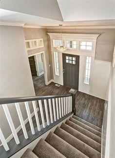 Entryway with gray stair rail and white ballusters. Crystal entry chandelier. Tuftex carpet with Manningtons Restoration Collection laminate flooring in Black Forest Oak fumed. Benjamin Moore Kendal Charcoal front door with White Dove trim. Transom windows above door frames. #entryway