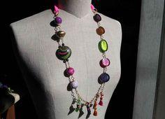 Collana con resine trasparenti, perle in legno ricoperte in carta e nappine multicolor.