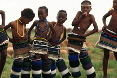 Africa | Young Ndebele girls blow plastic whistles as they dance. They are wearing ingholwani, thick grass rings covered with beads worn around their limbs and torso and the 'children's' square, beaded apron worn at the waist called amaghabi (iphephetu for older children). Mathula, South Africa | © Lindsay Hebberd/Corbis