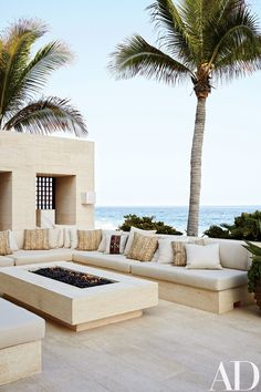 Made of niwala limestone from Spain, the outdoor living room's seating is topped by cushions clad in a Ralph Lauren Home fabric.