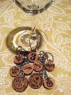 DIY Wine Charms. Cut the cork at about 1/4 to 1/3 of an inch. At least one side of the cut cork piece needs to be pretty smooth for stamping. Stamp the cork with waterproof ink and your favorite stamp, screw an eye hook into the top and thread a ball chain through the eye. Voila! Super easy, fun gifts for the holidays.