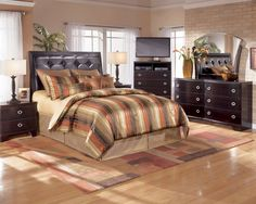 """Sophistication comes alive with the """"Pinella"""" bedroom collection. With nickel silver color crossbars accenting the dark merlot finish over replicated mahogany grain, this bedroom collection adds a rich sophisticated style to any bedroom. This collection features reeded moulding, reeded ring pulls and a shapely beveled mirror."""